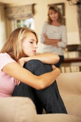 42164584 - grumpy teenage daughter sitting on sofa with mother in background